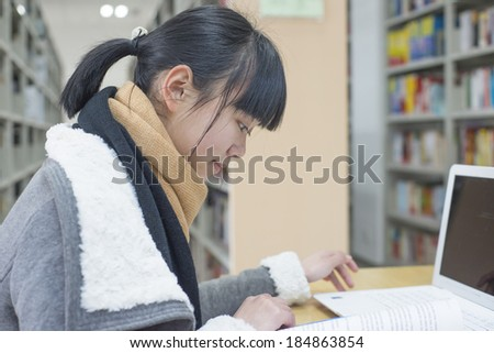 Chinese girl reading using a computer in the library - stock photo