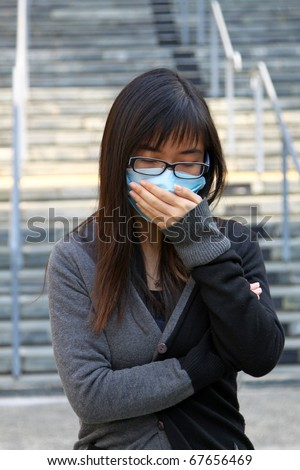 Chinese girl sick and wearing mask - stock photo
