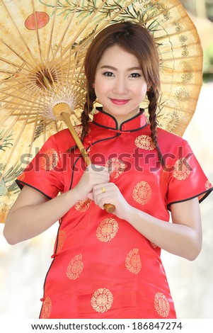 Chinese girl with dress traditional Cheongsam in Garden - stock photo