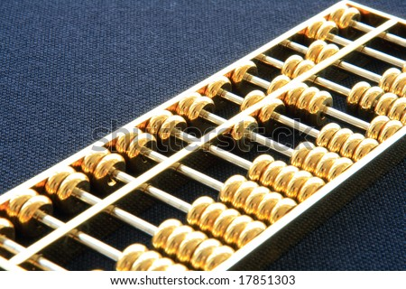 chinese golden abacus against a black ground - stock photo