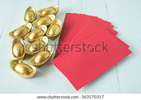 Chinese golden ingots and red envelope on wooden table : Chinese new year theme