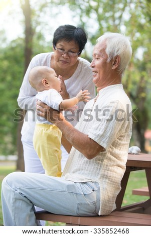 chinese grandfather and grandmother playing with baby grandson at outdoor