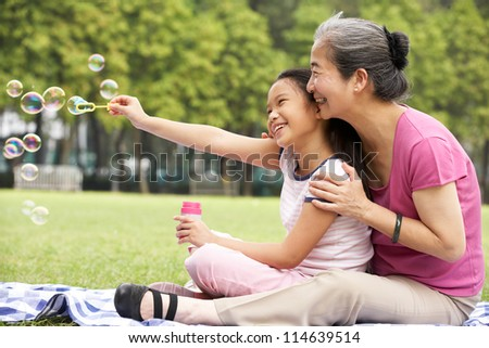 Chinese Grandmother With Granddaughter In Park Blowing Bubbles - stock photo