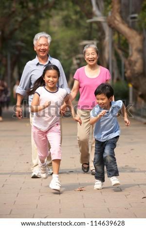 Chinese Grandparents Walking Through Park With Running Grandchildren - stock photo