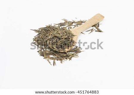 Chinese green tea spread out on bamboo spoon. The long and flat leaves, pan roasted by hand are named Longjing tea or literal translated to Dragon Well Tea. Isolated on white background.