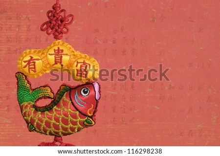 Chinese Hanging Fish Decoration on Old Red Chinese Calligraphy Background. Chinese New Year.