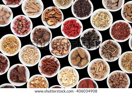 Chinese herb selection used in traditional alternative herbal medicine in porcelain bowls over black background. - stock photo