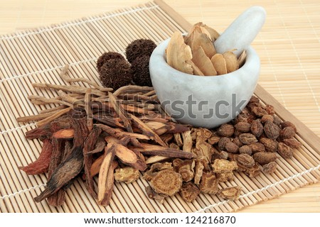 Chinese herbal medicine selection in a marble mortar with pestle and loose over bamboo mats. - stock photo