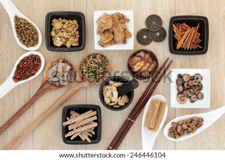 Chinese herbal medicine selection with I ching coins, mortar with pestle and chopsticks over light oak background. - stock photo