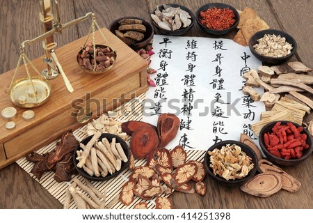 Chinese herbal medicine with herbs, scales and calligraphy. Translation reads as, chinese herbal medicine as increasing the bodys ability to maintain body and spirit health and balance energy. - stock photo