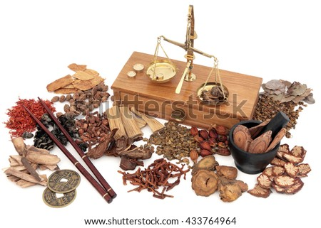 Chinese herbal medicine with traditional herb ingredients and old brass scales over white background.