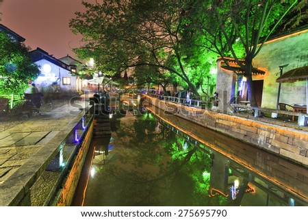 Chinese historic city Suzhou - ancient canals illuminated at sunset surrounded by historic tea houses - stock photo