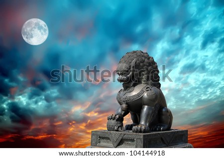 Chinese Imperial Lion Statue in the night sky - stock photo