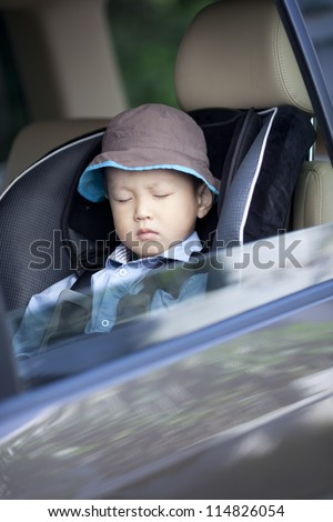 Chinese little boy sleeping in the car