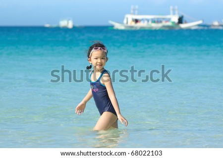 Chinese little girl playing on the beach - stock photo