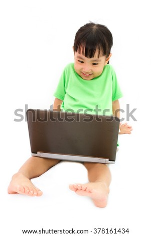 Chinese little girl sitting on floor with laptop in plain isolated white background.