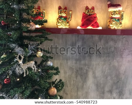 Chinese lucky cat or Maneki Neko with Santa outfit beside Christmas tree
