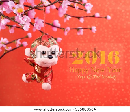 Chinese lunar new year ornaments toy of monkey on festive background - stock photo