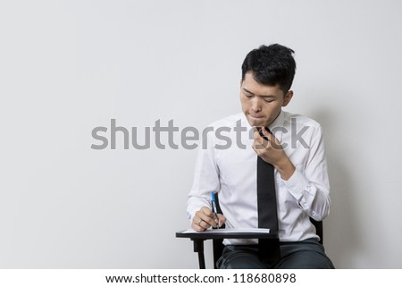 Chinese male student or business man taking an exam test - stock photo