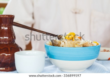 Chinese man eat vegetarian casserole rice on dining table. This is food for vegetarian festival. No meat and fish