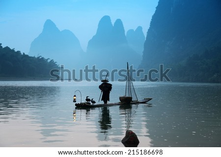 Chinese man fishing with cormorants birds , traditional fishing use trained cormorants to fish in China - stock photo
