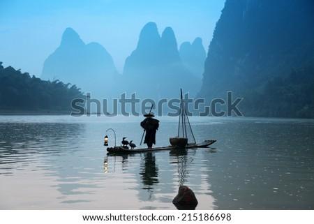 Chinese man fishing with cormorants birds , traditional fishing use trained cormorants to fish in China - stock photo