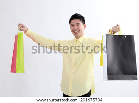chinese man holding few colorful shopping bags