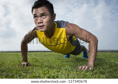Chinese man performing push up in the city park. Male fitness concept. - stock photo