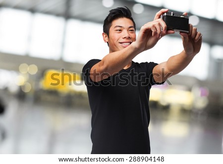 chinese man taking a photo with camera - stock photo