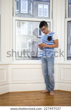 Chinese Man using his phone at home in the lounge.