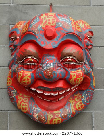 chinese mask on wall on Liulichang street in Beijing, China - stock photo