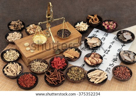 Chinese medicine ingredients with scales and calligraphy.  Translation reads as chinese herbal medicine as increasing the bodys ability to maintain body and spirit health and balance energy. - stock photo