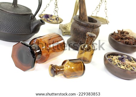 Chinese medicine with herbs and apothecary bottle on light background