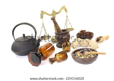 Chinese medicine with herbs and scale on light background - stock photo