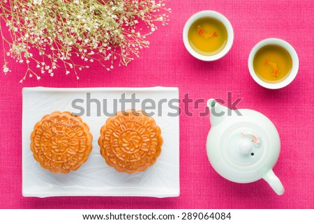 Chinese mid autumn festival foods. Traditional mooncakes on pink background. Mooncake and tea. - stock photo