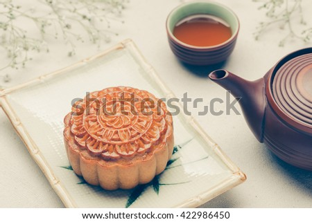 Chinese mid autumn festival foods. Traditional mooncakes on table setting with teacup. - stock photo