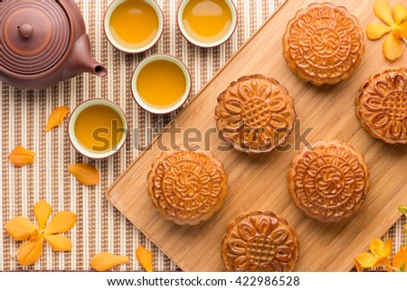 Chinese mid autumn festival foods. Traditional mooncakes on table setting with teapot. - stock photo