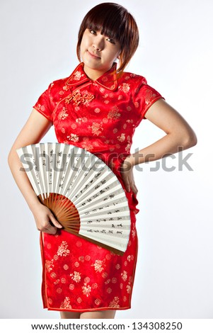 Chinese model in traditional Cheongsam dress with slit, holding fan. Asian cute girl, young model with a variety of facial expressions and poses.