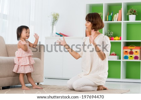 Chinese mother and daughter playing clapping game - stock photo