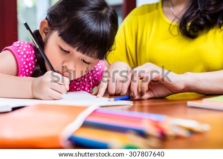 Chinese mother homeschooling her child teaching her daughter to write - stock photo