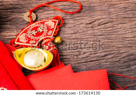 Chinese new year decoration, ancient Chinese golden ingots, tassel and red pocket in Chinese red bag on wooden table - stock photo