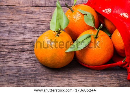 Chinese new year decoration, mandarine oranges in Chinese red bag on wooden table - stock photo