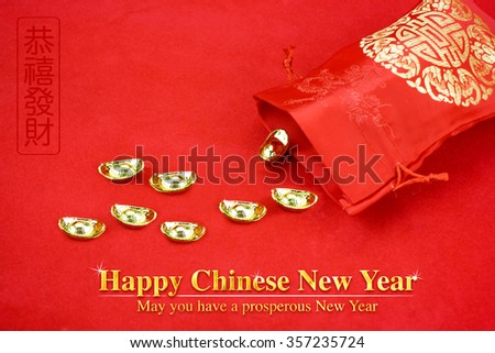 "Chinese new year decoration: red fabric packet or ang pow with chinese style pattern and golden coin and ingots on red felt fabric,  Chinese Language mean ""May you have a prosperous New Year"". - stock photo"