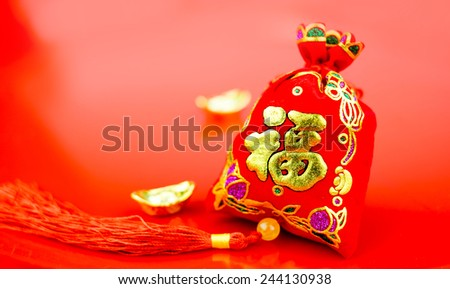"""Chinese new year decoration: red felt fabric bag or ang pow with word """" prosperous """" and golden ingots on red glossy floor - stock photo"""