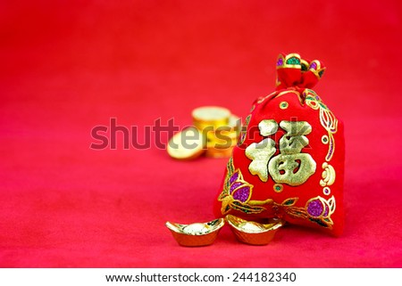 """Chinese new year decoration: red felt fabric bag or ang pow with word """"prosperous"""" and golden ingots on red fabric - stock photo"""