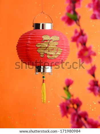 Chinese new year decoration--Red lantern and peach blossom on a festive background. - stock photo