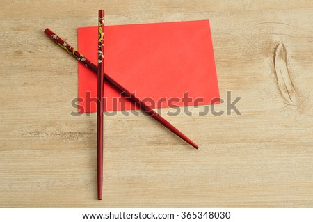 Chinese New Year design. A red envelope for money in the Chinese New Year isolated on a wooden background with chopsticks - stock photo