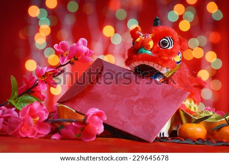 Chinese new year festival decorations, miniature dancing lion and ang pow or red packet with copy space ready for text, on glitter red background.  - stock photo