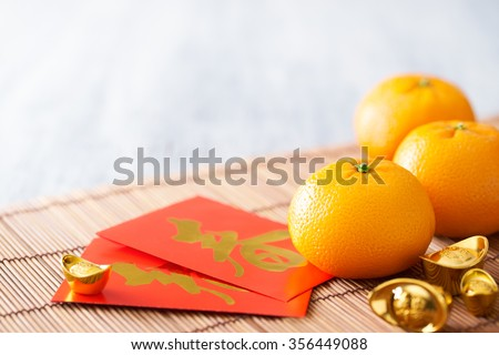 Chinese New Year - Mandarin orange, gold sycee (Foreign text means wealth) and red packet (Foreign text means spring season) on white painted wood table - stock photo