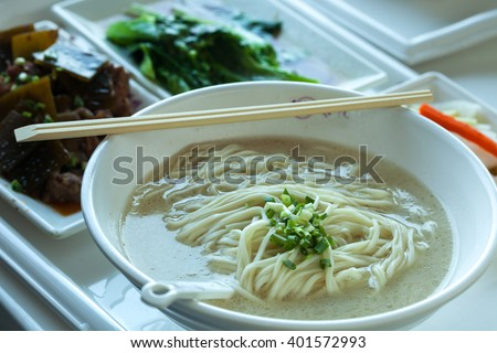 Chinese Noodle with hot soup in a bowl and side dishes.